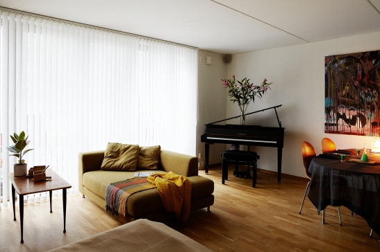Vardagsrum soffa kuddar pläd piano