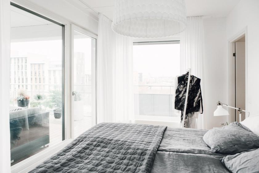 säng sovrum grått vitt utsikt