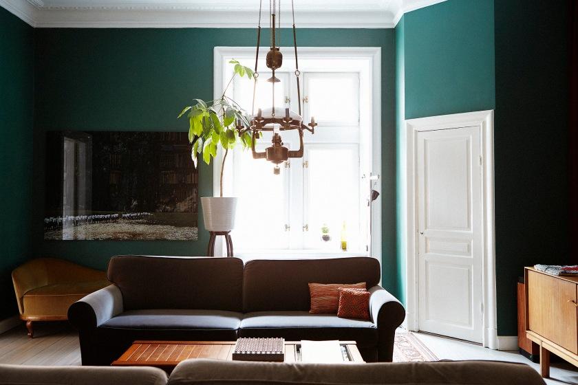 Vardagsrum grönt soffa sammet lampa fönster växt sekelskifte