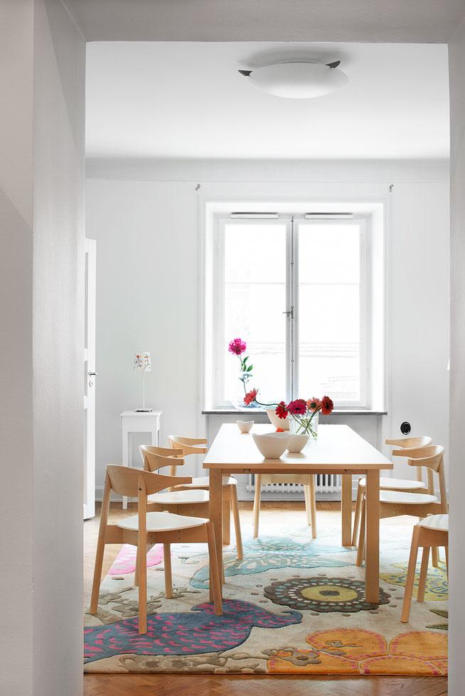 Matbord stolar blommor fönster