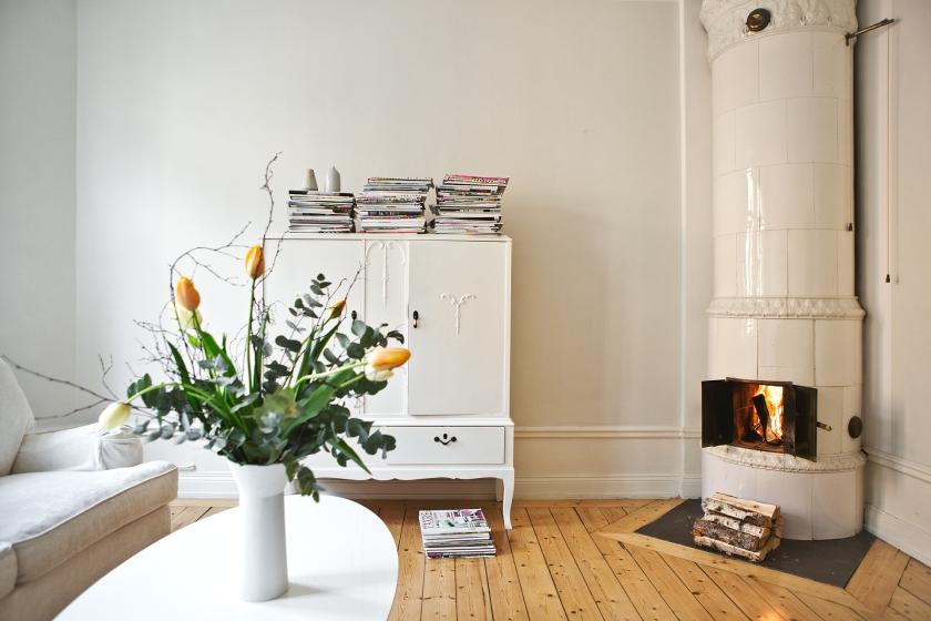 Blommor kakelugn sekelskifte byrå soffbord vardagsrum