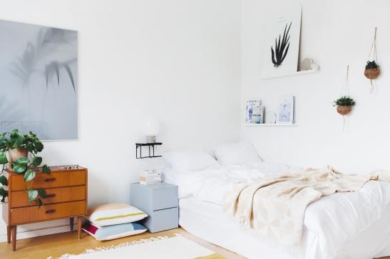 Säng sovrum konst växter byrå kuddar filt