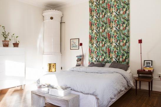 Säng sovrum tyg kakelugn nattygsbord lampa dekoration