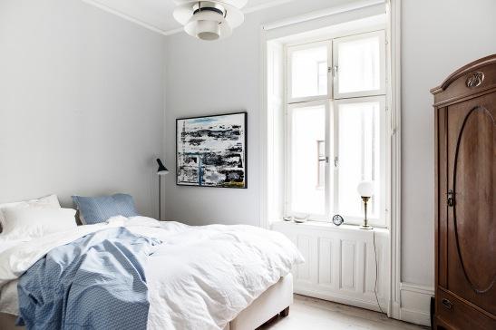 sovrum säng blått lakan konst