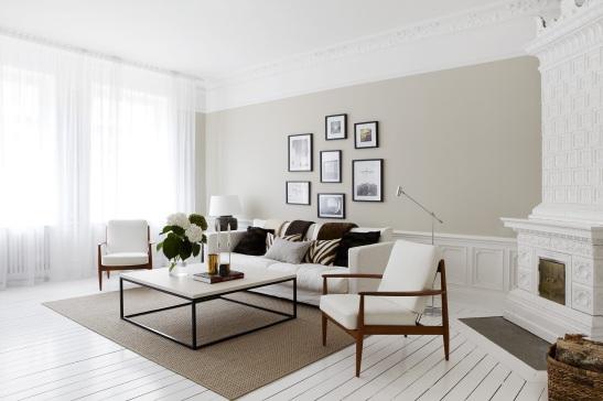 Vardagsrum kakelugn soffa soffburd fåtölj konst gardin