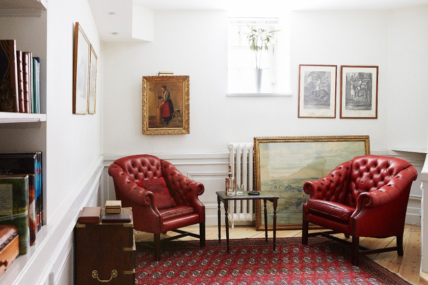 Vardagsrum rött skinn fåtölj matta konst klassisk