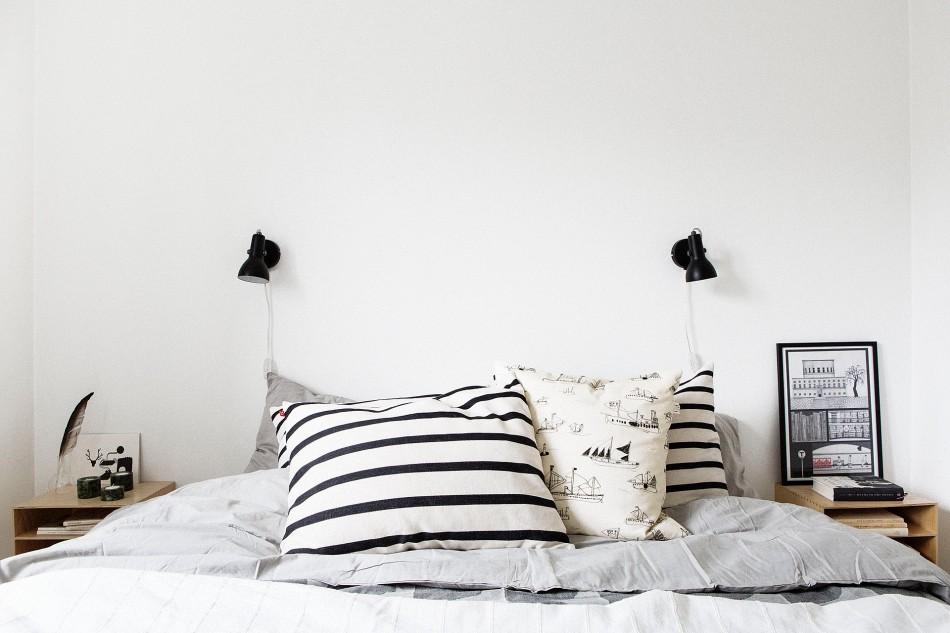 Säng kuddar randigt överkast lampor sovrum
