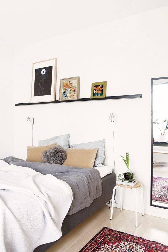 Säng tavla spegel kuddar nattygsbord sovrum