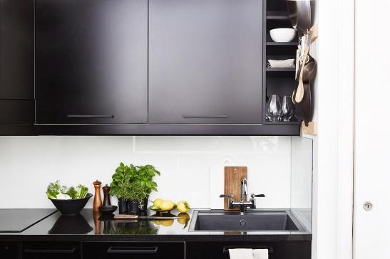 Östermalm kök svarta matta skåpsluckor svart blank bänk