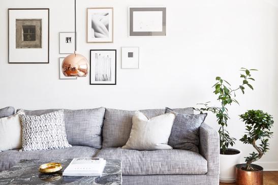 Östermalm vardagsrum kopparlampa tavelvägg soffa soffbord marmor