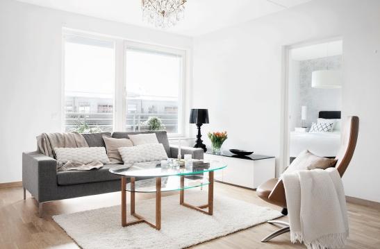 Hammarby sjöstad vardagsrum glasbord träben soffa ljuskrona