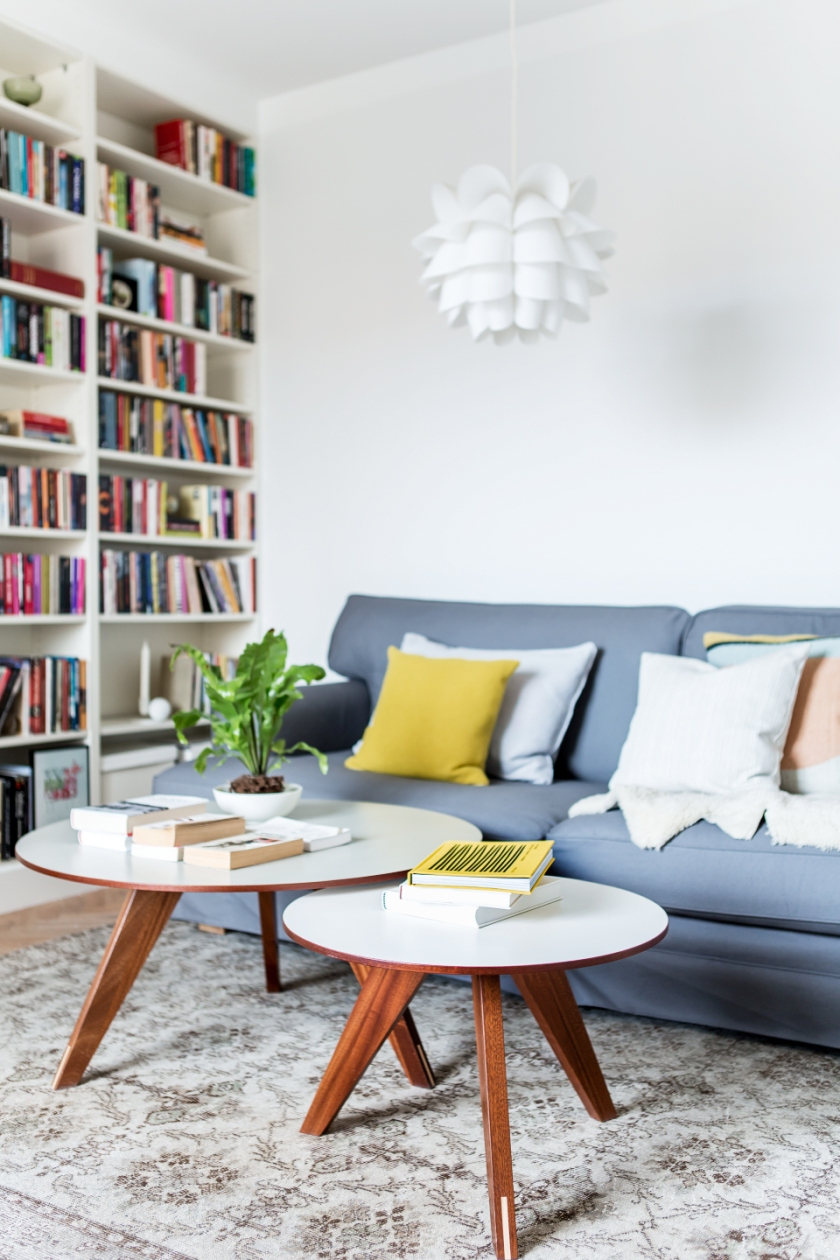 Kungsholmen vardagsrum soffa bokhylla runda bord träben
