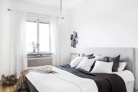 Stora Essingen sovrum trägolv fotovägg vita gardinger vita kuddar pläd