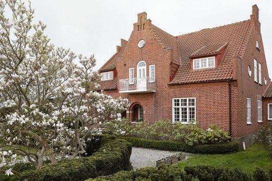 Österlen doktorsvilla rött tegel vita fönster blomstrande trädgård