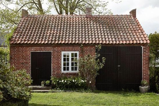 Österlen uthus tegel svart stalldörr vita korsfönster