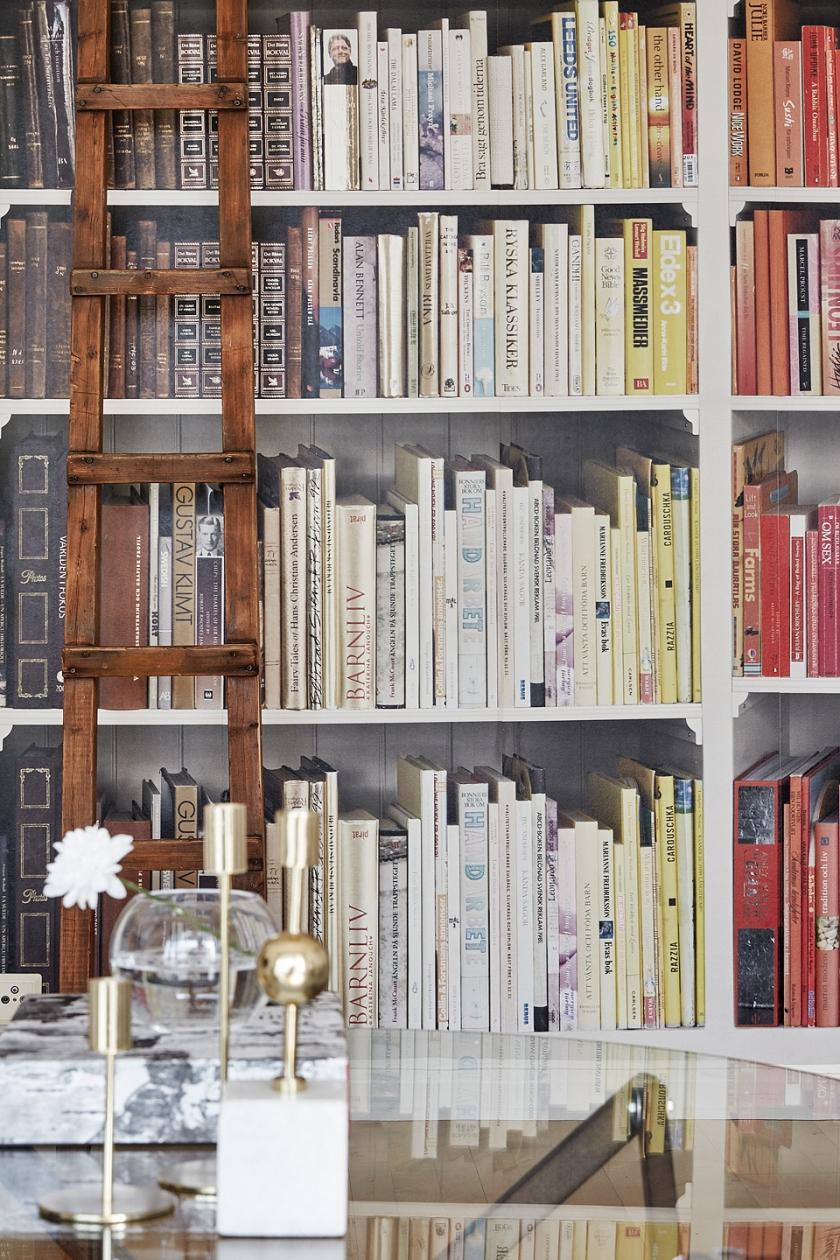 Hammarby sjöstad vardagsrum trästege glasbord välsorterad bokhylla böcker