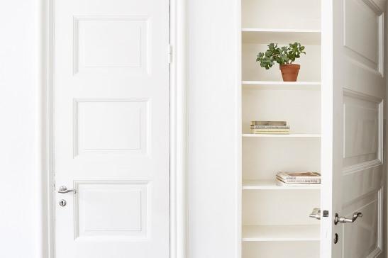 Kunghsolmen vardagsrum platsbyggd bokhylla spegeldörr vitt snickeri