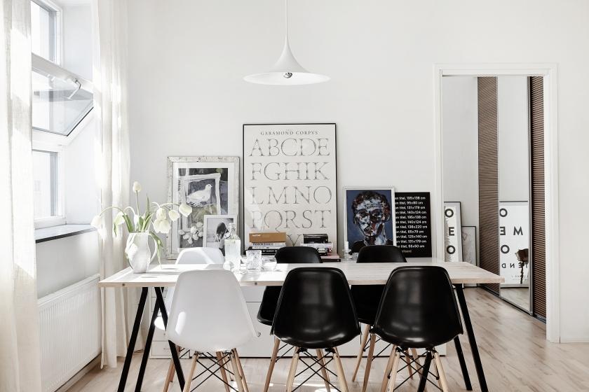 Södermalm vardagsrum matbord stolare eames svart vitt tavelvägg träbord