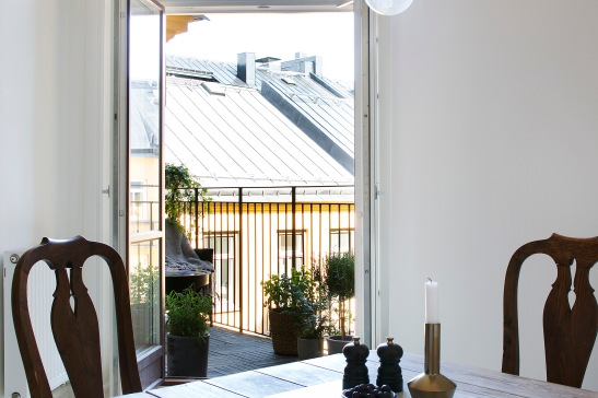 Sofo vardagsrum matbord trästolar utsikt mot balkong räcke