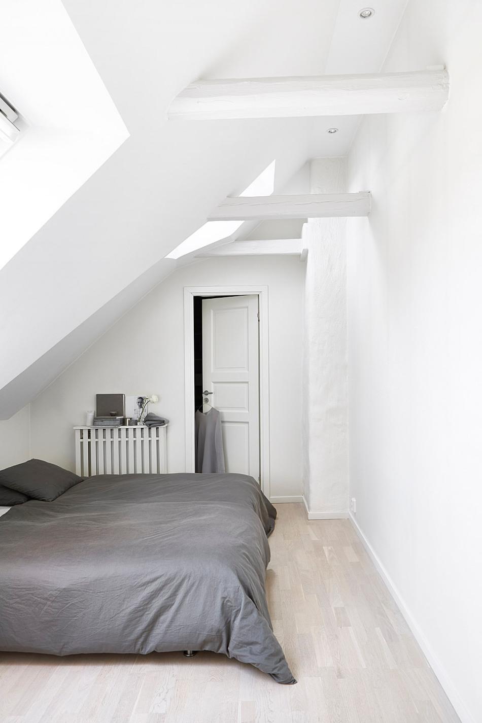 Vasastan sovrum snedtak vitmålade bjälkar hotellbäddad säng