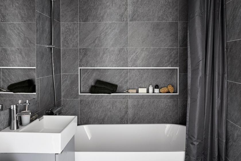 Södermalm badrum vitt badkar grått kakel drapperi